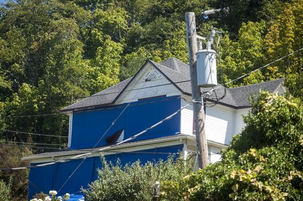 "In this photo taken on Aug. 17, 2015, the home featured in the 1985 classic ""The Goonies"" is covered in blue tarps to deter fans from getting too close to the house, in Astoria, Ore. The home gets up to 1,500 visitors daily, and the property owner is asking for relief. Joshua Bessex /Daily Astorian via A"