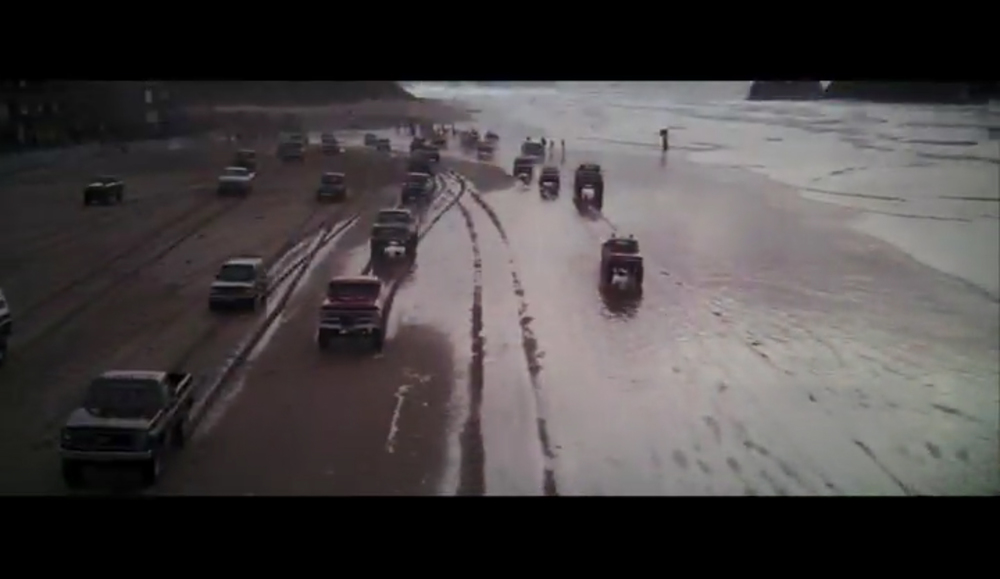 Screenshot of the car racing / truck rally opening sequence in The Goonies filmed by Haystack Rock on Cannon Beach.