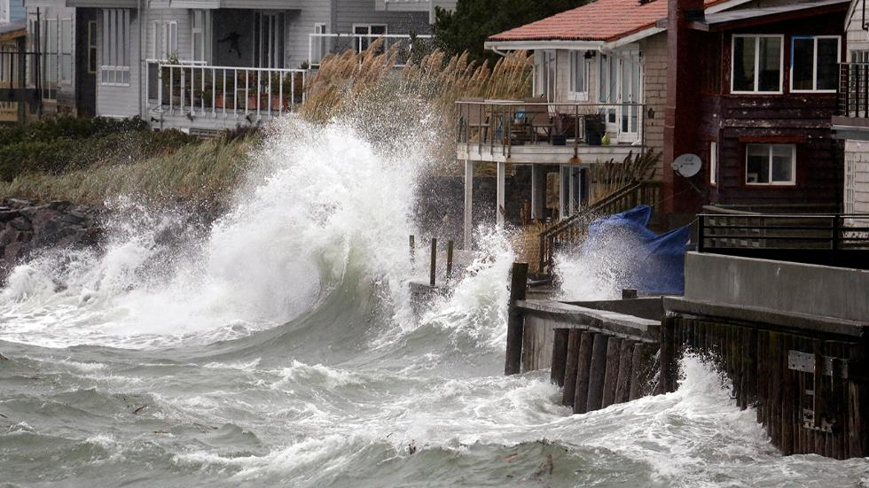 Wind-blown waves batter houses Nov. 17, 2015, in Seattle. (AP Photo/Elaine Thompson)