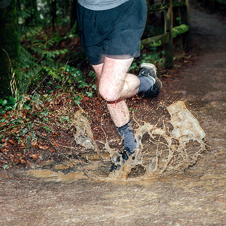 crosspoint-waterproof-wool-socks-runner-splashing-in-mud-cropped