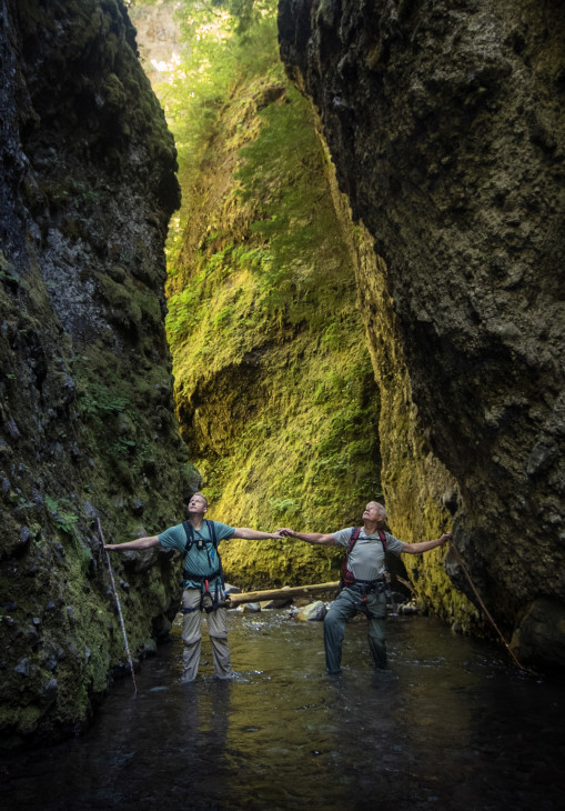 A slot canyon is casually defined as more narrow than tall. Sean Malone, left, and Mike Malone, right, stand at a point in the canyon where it is only two arm spans wide. Uncage The Soul/OPB