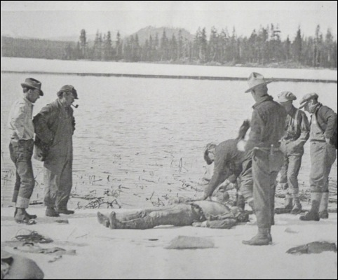 Concerned family members, friends, and members of the search party look on as Deschutes County Coroner C. P. Niswonger examines the body of one of the victims at the recovery scene at Big Lava Lake.