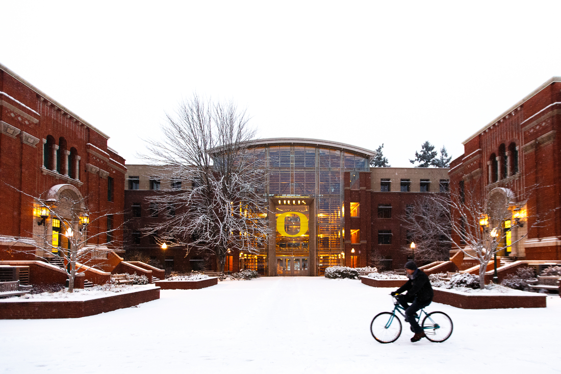 The Lillis Business Complex at the University of Oregon sits with a fresh coat of snow as a bicyclist sloshes by in Eugene, Ore. on Dec. 6, 2013. (Ryan Kang/Emerald)