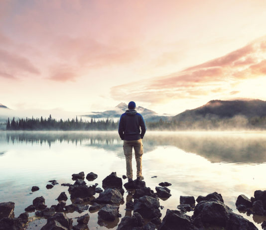 A man at sunrise standing in front of Sparks Lake near Sunriver Oregon