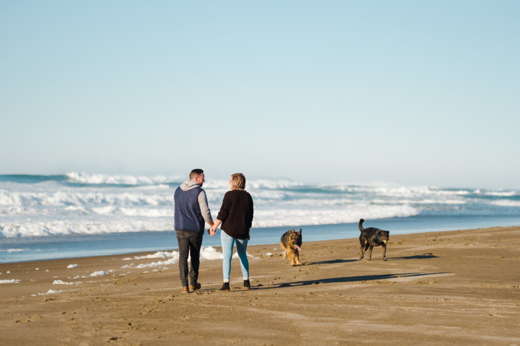 A couple and their dogs walking along the Oregon Coast