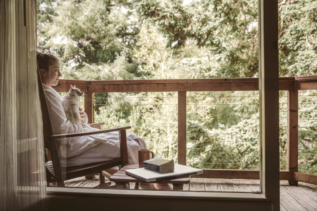 A woman relaxing on the patio of a private room at Salishan Coastal Lodge on the Oregon Coast