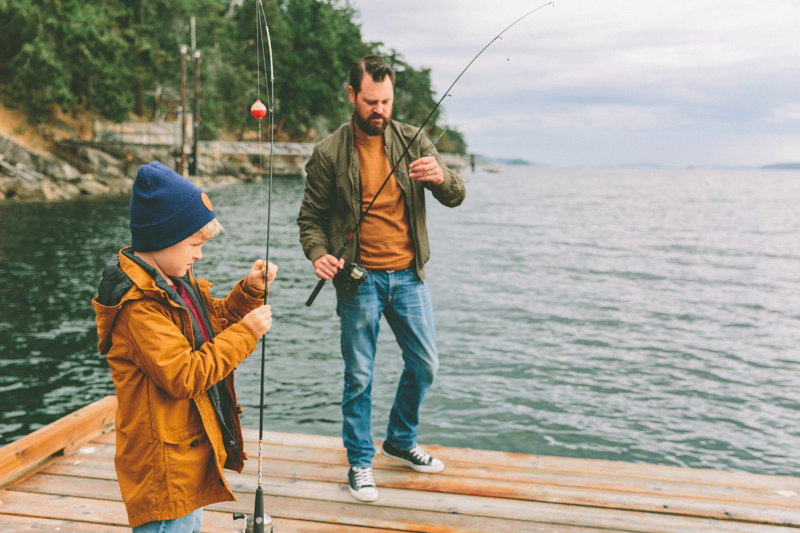 A father and son fishing off a dock at a lake
