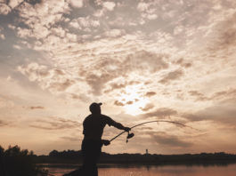 A man fishing in a lake at sunset