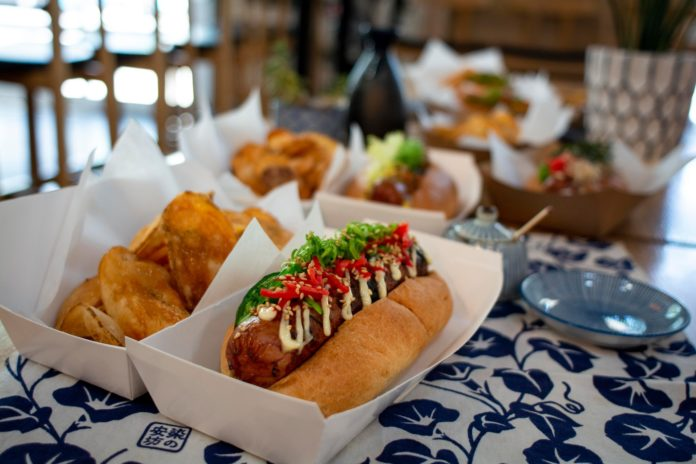 A delicious looking Kemuri Japanese hotdog with toppings and fresh chips in Portland Oregon.