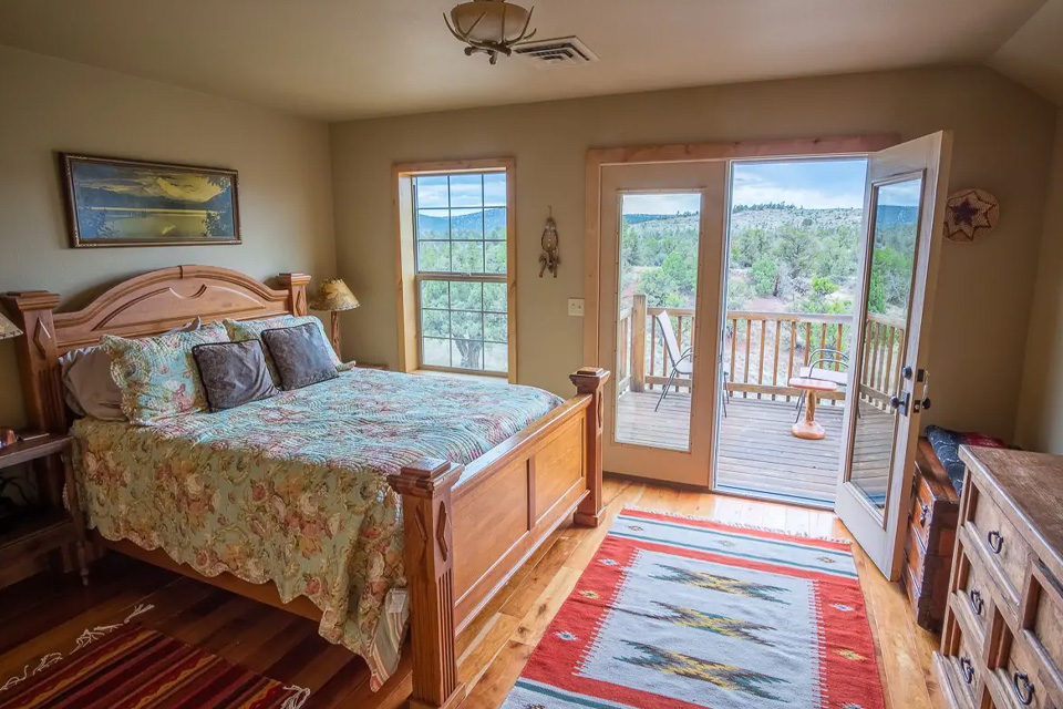 A bed with an open door to a porch