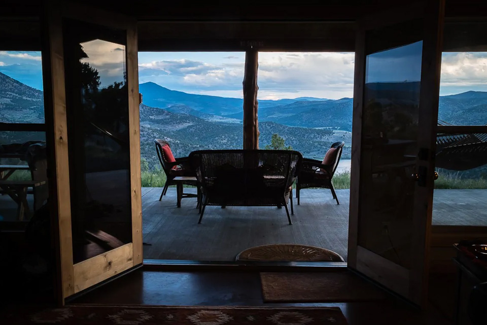Looking out the open doors of the cabin to the front porch and high desert view