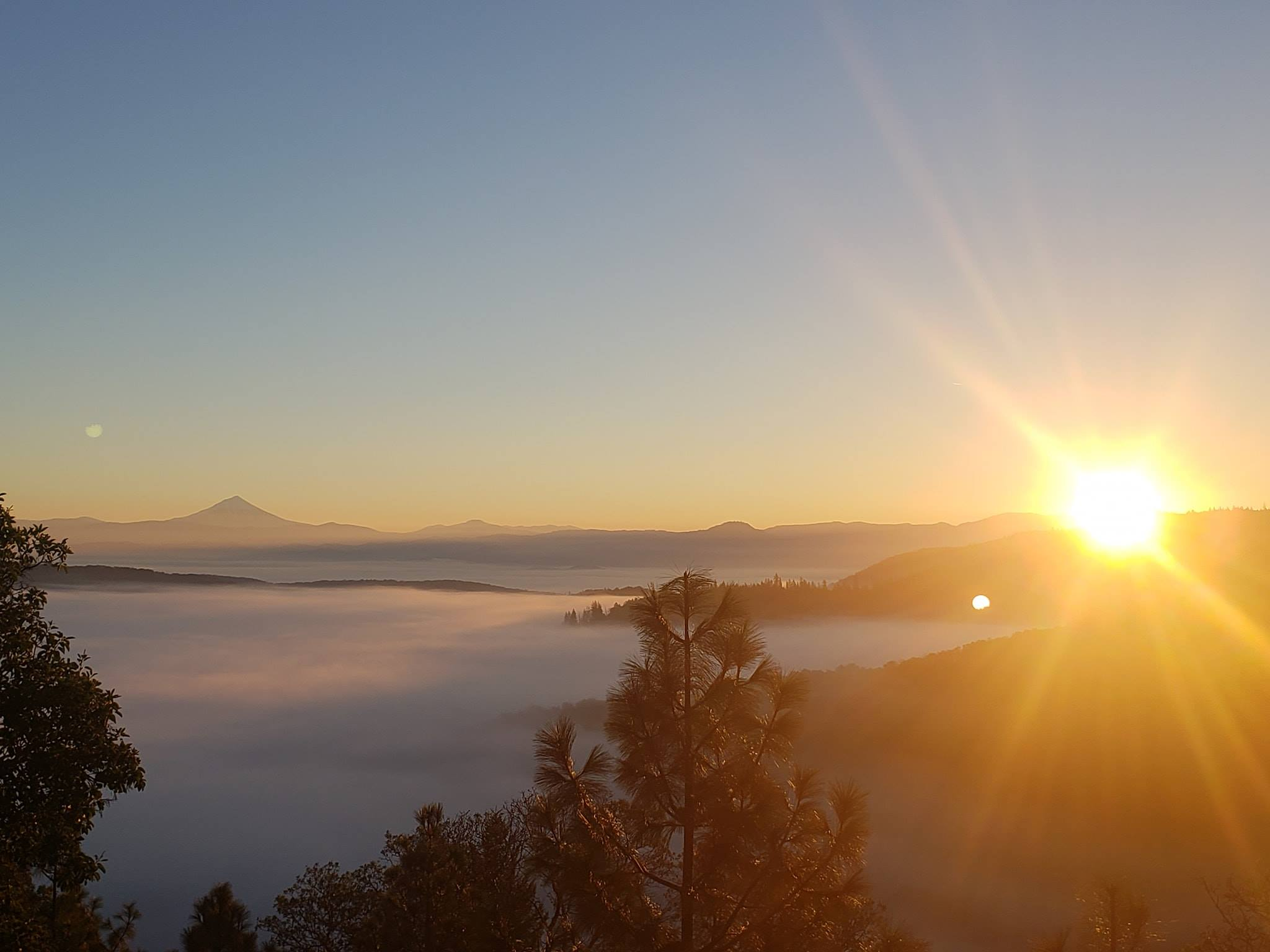 View of the sunrise over mountains and a valley of fog