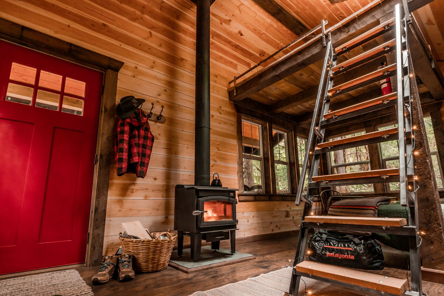 The cabin interior with the woodstove and ladder to the loft bed