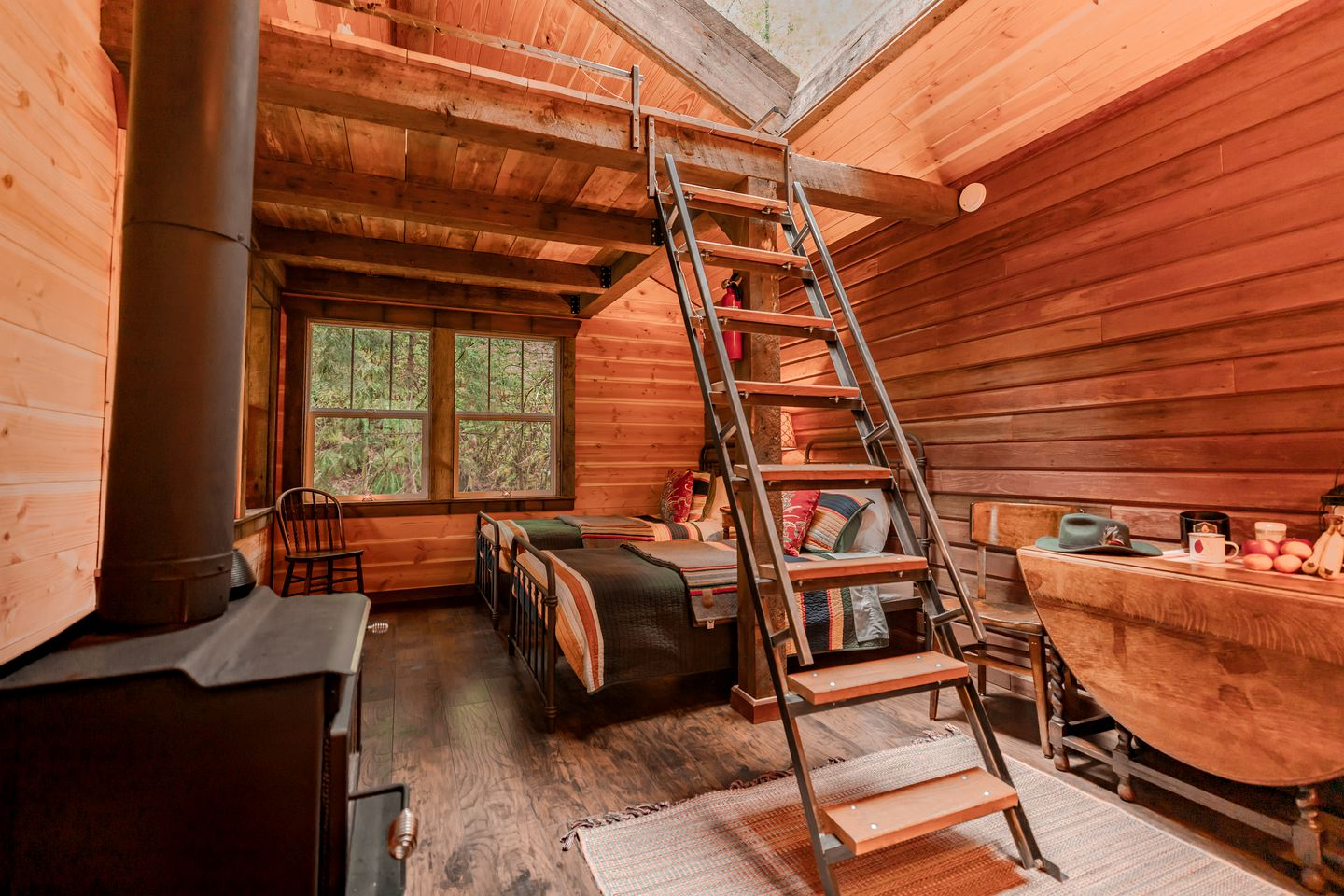 The cabin interior with two beds and a ladder to the loft bed