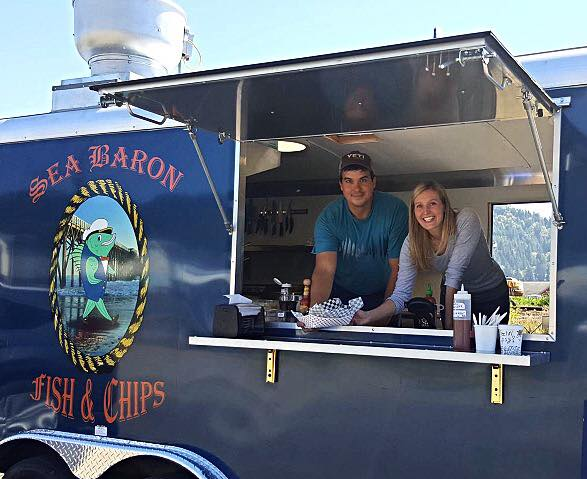Two people working inside the Sea Baron food truck.