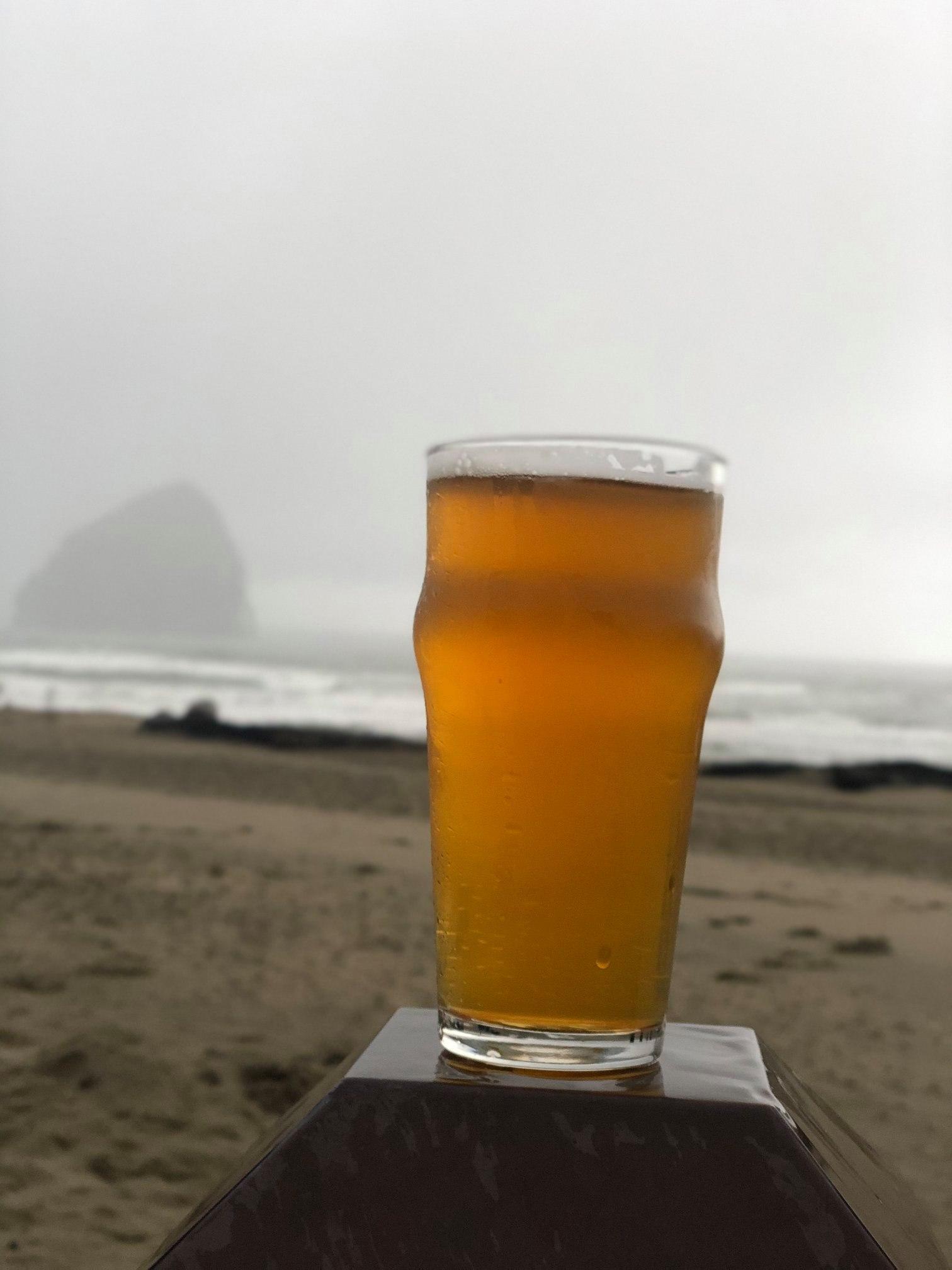 Beer in front of Haystack Rock on the Oregon coast.