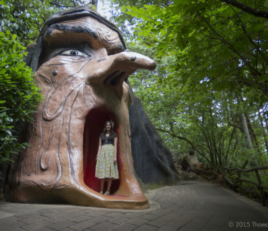 A large witches head with a woman standing in the mouth.