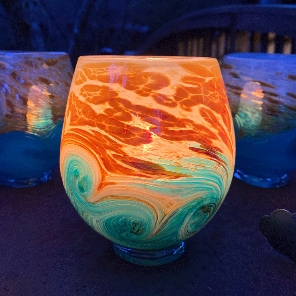 Handmade glass in teals and oranges.