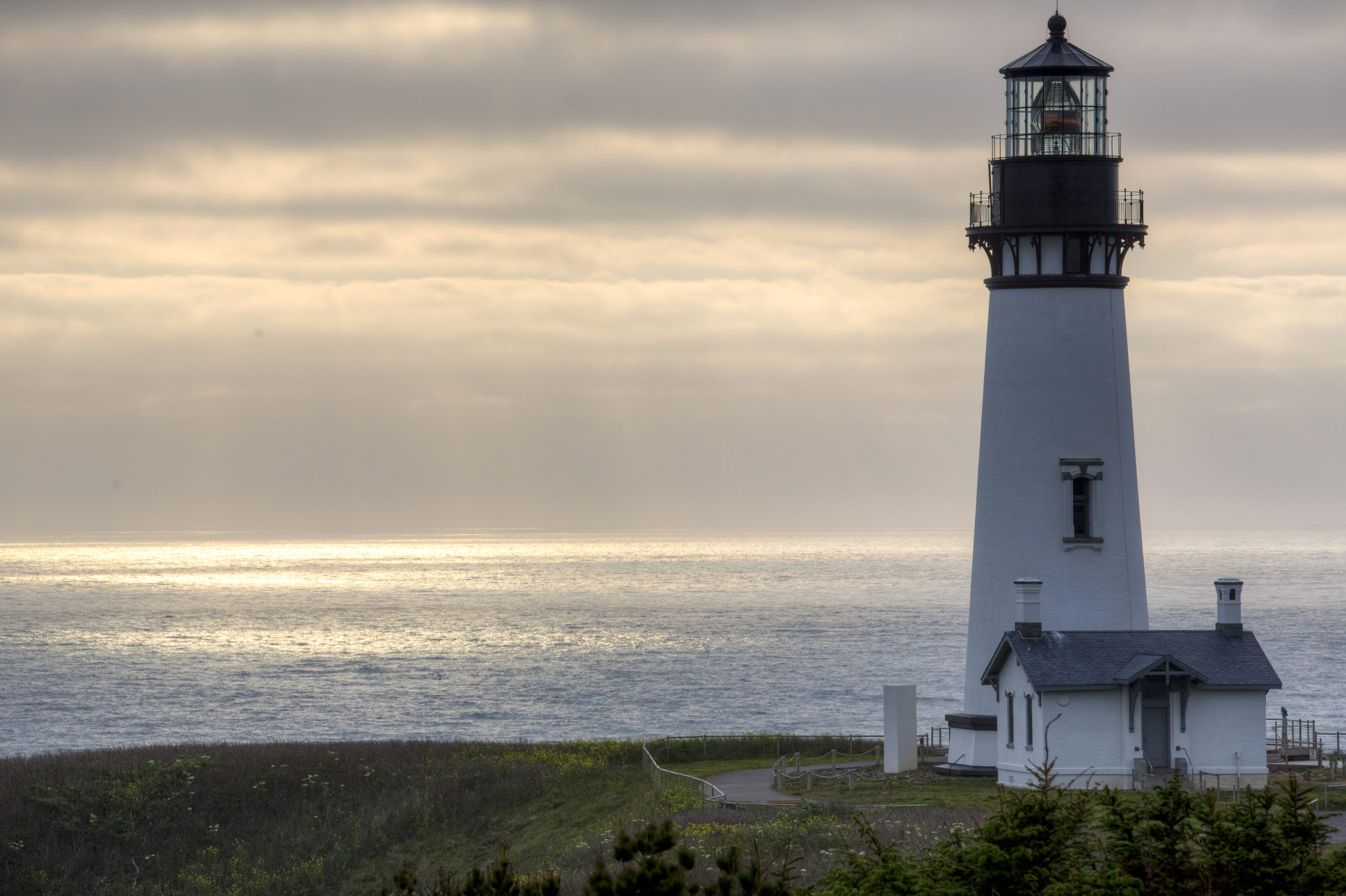 A white lighthouse at sunset overlooking the Pacific Ocean in Oregon.