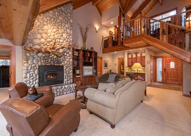 The inside of a gorgeous cabin with a rock fireplace in Sunriver Oregon.