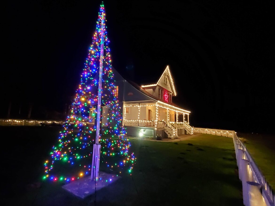 a christmas tree in front of holiday decorated heceta head lightkeepers cottage