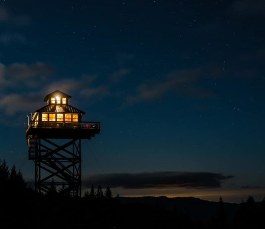 The lookout tower lit up at night under the stars