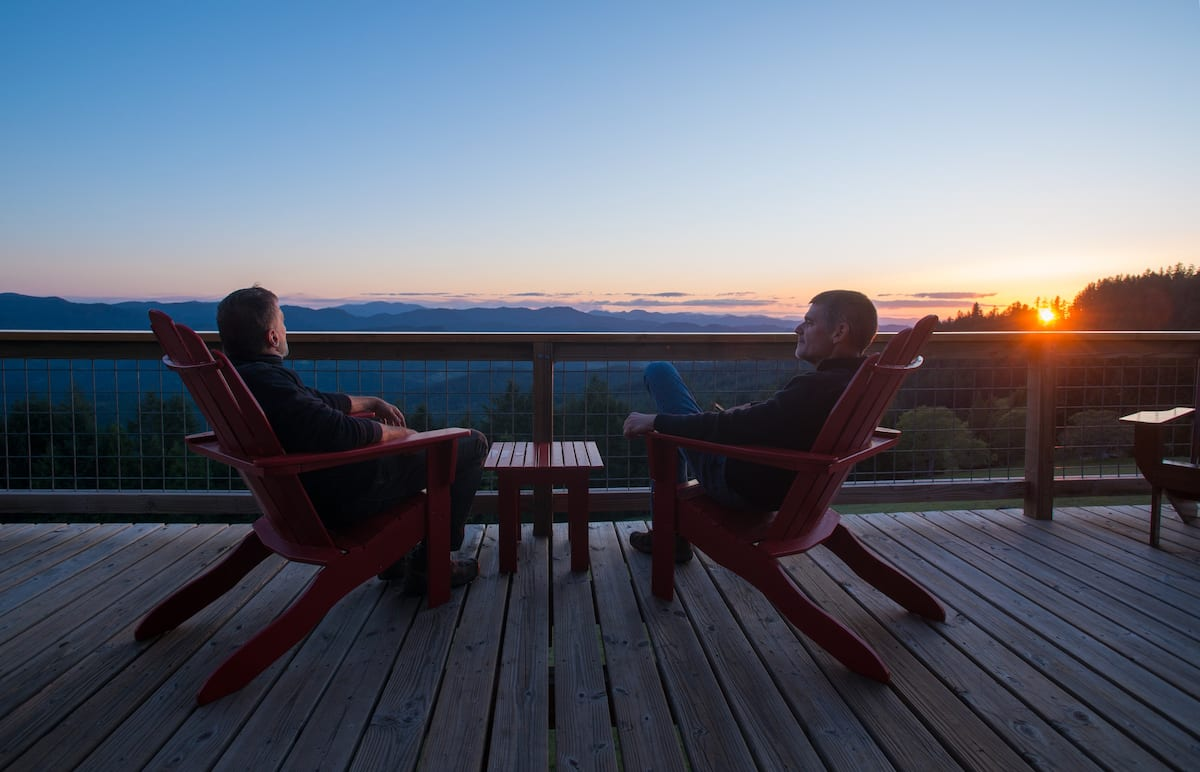 Two people sitting on the deck enjoying a sunset.