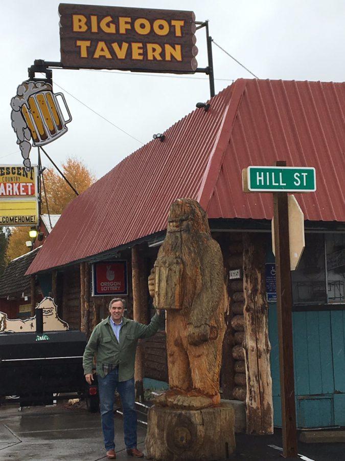 oregon senator jeff merkley next to carved bigfoot statue