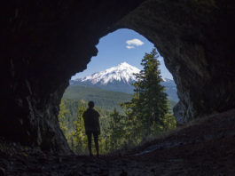 A man in a cave looks out at Mt Jefferson in Oregon.