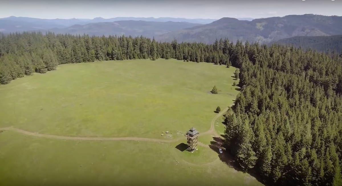 An aerial view of the meadow and lookout tower airbnb in Oregon