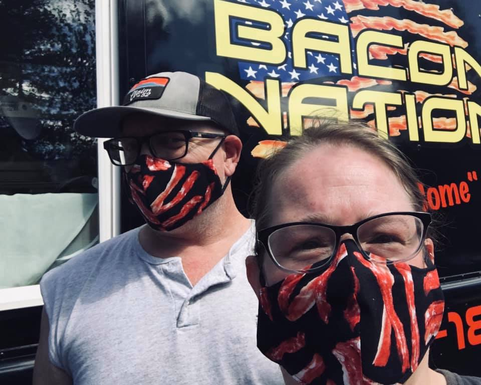 A man and a woman wearing bacon masks at the bacon nation food truck in eugene