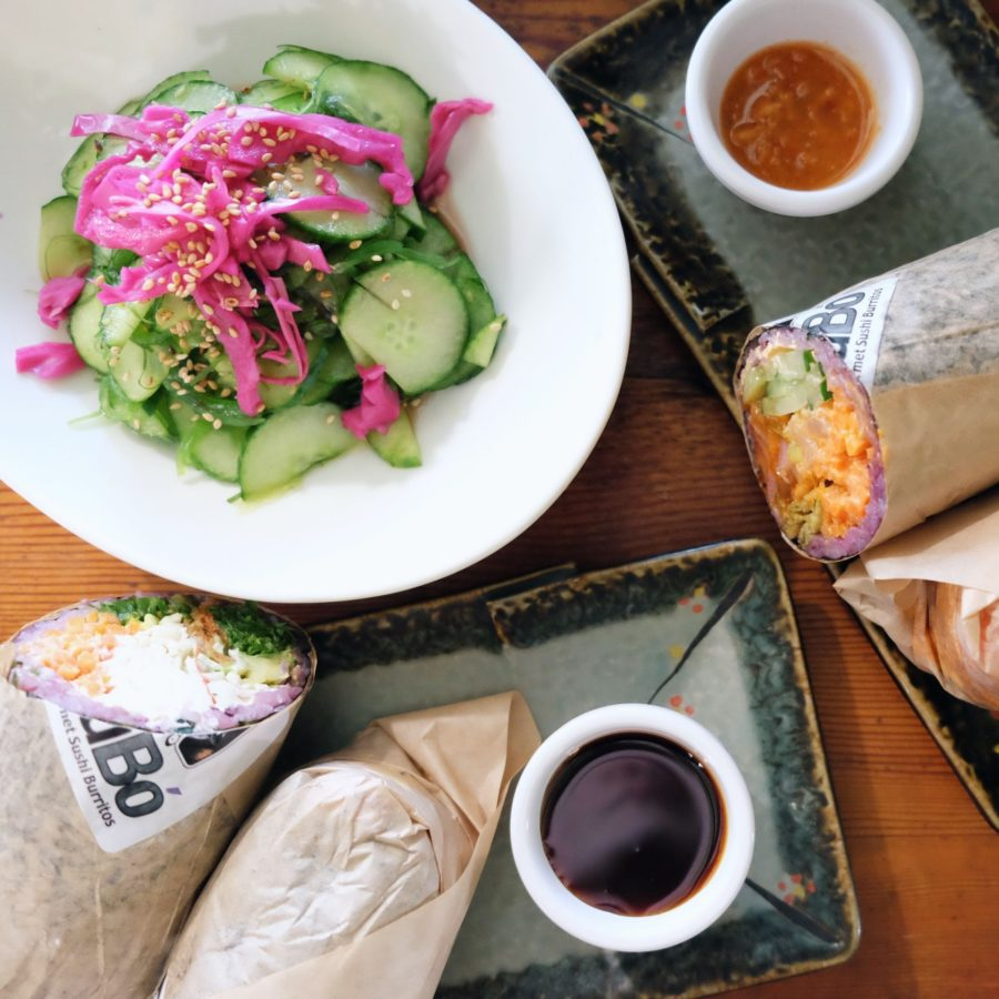 sushi burritos arranged on a table with cucumber salad and sauces